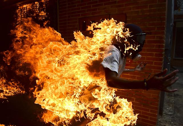 <p>An opposition activist suddenly turned into a human torch runs upon clashing with riot police during a protest against Venezuelan President Nicolas Maduro, in Caracas on May 3, 2017. (Photo credit should read RONALDO SCHEMIDT/AFP/Getty Images) </p>