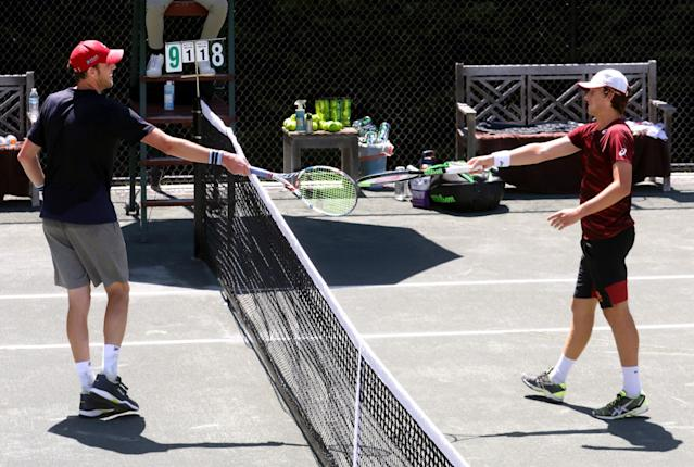 """Sam Querrey, left, and Brandon Holt touch rackets instead of shaking hands after Querrey wins the final round of the Homecourt Advantage. <span class=""""copyright"""">(Genaro Molina / Los Angeles Times)</span>"""