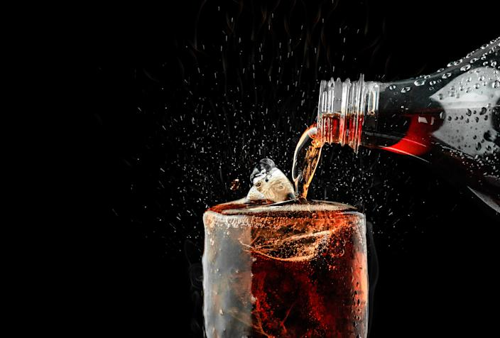 Pour soft drink in glass with ice splash on dark background.