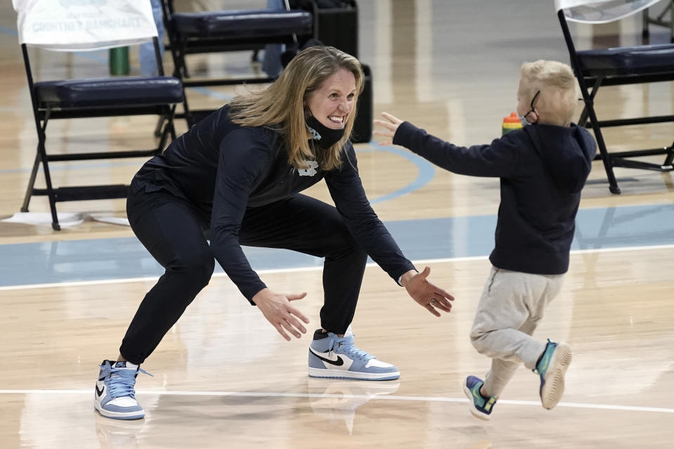 North Carolina head coach Courtney Banghart reaches to hug her son Tucker, 6, following an NCAA college basketball game against North Carolina State in Chapel Hill, N.C., Sunday, Feb. 7, 2021. (AP Photo/Gerry Broome)