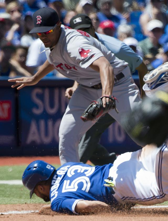 Toronto Blue Jays' Melky Cabrera (53) is tagged out at third base by Boston Red Sox third baseman Xander Bogaerts, top, during second inning baseball action in Toronto on Thursday, July 24, 2014. (AP Photo/The Canadian Press, Nathan Denette)