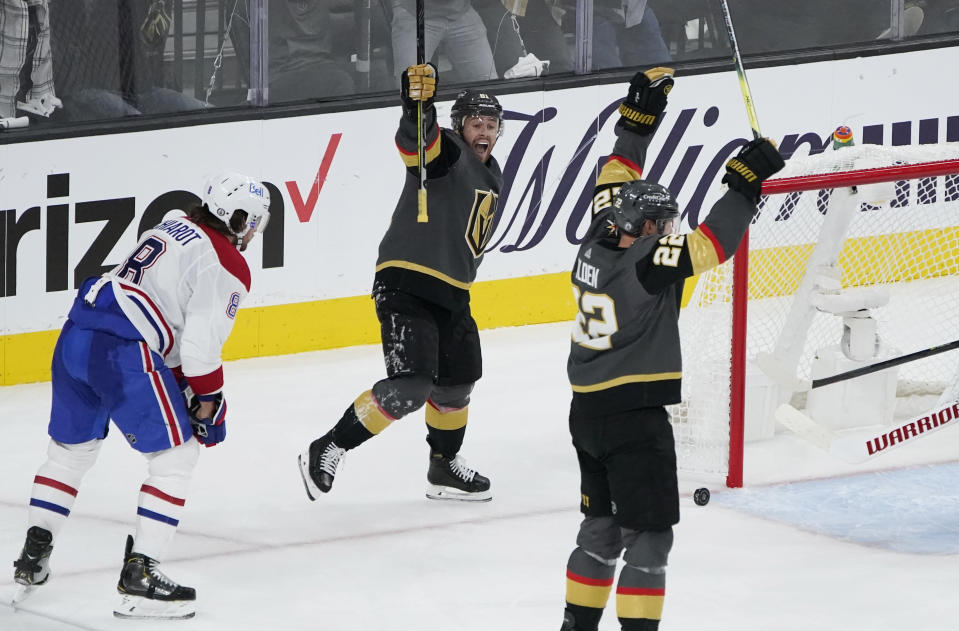 Vegas Golden Knights center Jonathan Marchessault, center, celebrates after Vegas Golden Knights defenseman Nick Holden, right, scored against the Montreal Canadiens during the third period in Game 1 of an NHL hockey Stanley Cup semifinal playoff series Monday, June 14, 2021, in Las Vegas. (AP Photo/John Locher)