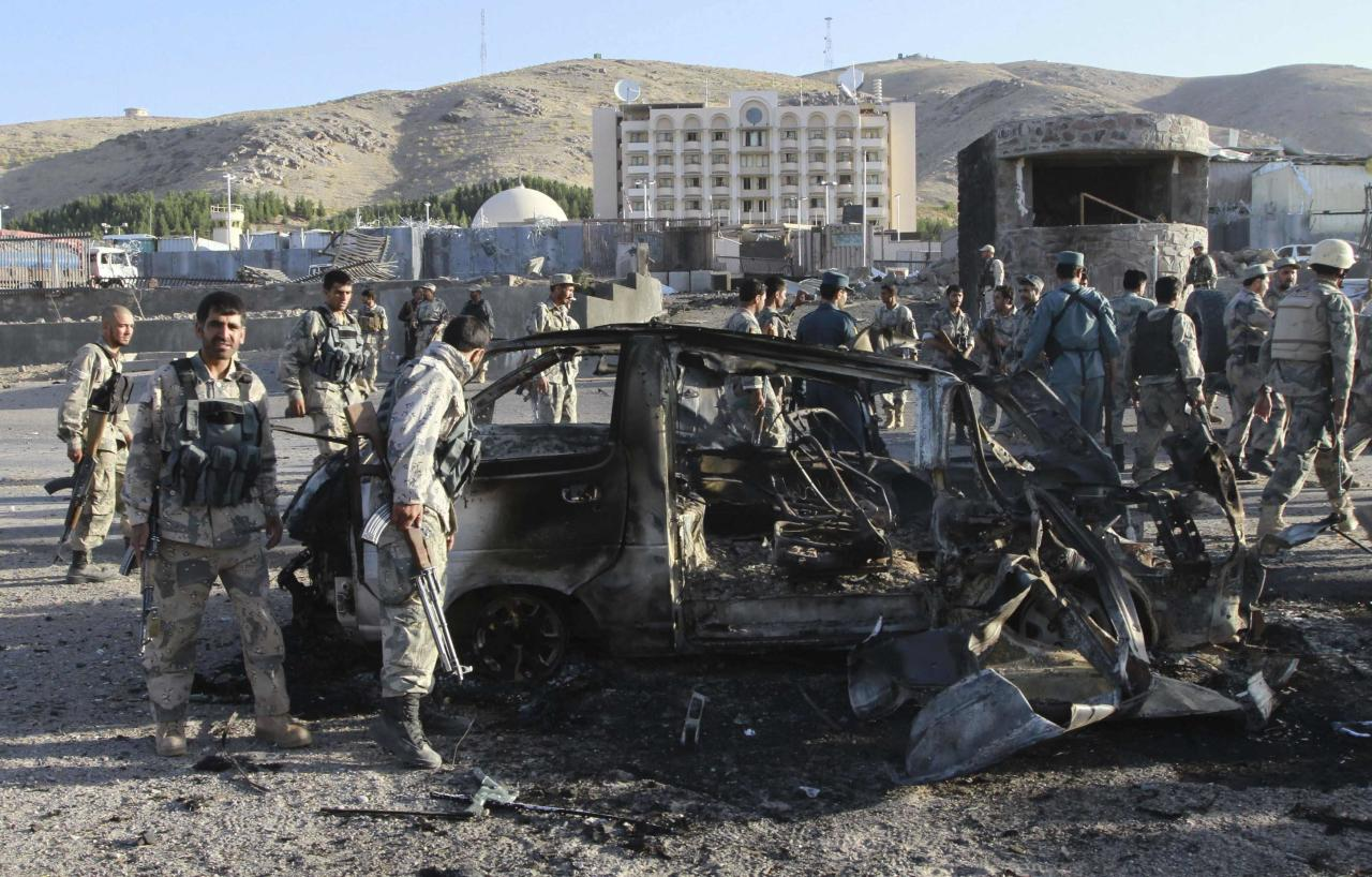 Afghan security forces inspect a damaged car, which was used during a suicide bomb attack, outside the U.S. consulate in Herat province September 13, 2013. At least three people were killed when insurgents attacked the U.S. consulate in Herat on Friday, detonating a powerful truck bomb outside the front gates and launching a gunbattle with security forces, officials said. REUTERS/Mohammad Shoib (AFGHANISTAN - Tags: CIVIL UNREST MILITARY POLITICS TPX IMAGES OF THE DAY)
