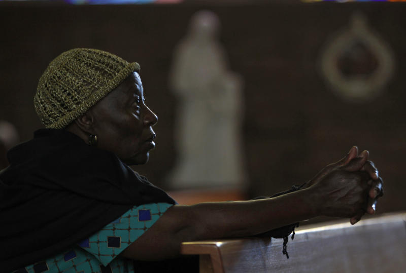 """A worshipper prays at the Regina Mundi Church in Soweto, South Africa, prior to early morning Mass, Tuesday, Dec 11 2012. Calls for prayer have been made for former president Nelson Mandela who was admitted to the 1 Military Hospital in Pretoria at the weekend. South Africa's presidency says former President Nelson Mandela is suffering from a recurring lung infection and is responding to treatment. The statement Tuesday, Dec. from presidential spokesman Mac Maharaj said the 94-year-old anti-apartheid icon is """"receiving appropriate treatment and he is responding to the treatment."""" (AP Photo/Denis Farrell)"""
