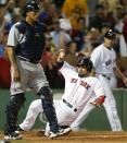 Boston Red Sox's Shane Victorino, center, scores the tying run on a single by Jonny Gomes as Seattle Mariners' Henry Blanco, left, walks toward the mound in the ninth inning of a baseball game in Boston, Thursday, Aug. 1, 2013. The Red Sox won 8-7. (AP Photo/Michael Dwyer)