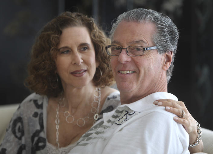 """In this Sunday, July 8, 2012 photo, Jason and Karin Marder pose for a picture in their home in New York. Jason Marder, who turned 70 on Tuesday, July 10, 2012, was diagnosed with Alzheimer's more than eight years ago. In the roughly five years that her husband has taken Gammagard, """"there has been decline"""" in his health but it is very minimal and the kind of slowing down you might expect from ordinary aging, she said. """"He travels the subways, he does things that you and I do. And our quality of life together is what's most important."""" (AP Photo/Seth Wenig)"""