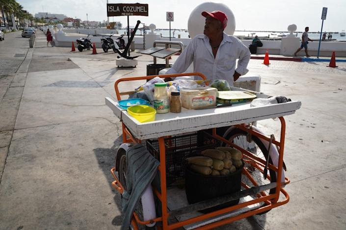 """A street vendor selling corn on the cob finds a dearth of customers outside the ferry terminal in Cozumel, Mexico. <span class=""""copyright"""">(Liliana Nieto del Rio / For The Times)</span>"""
