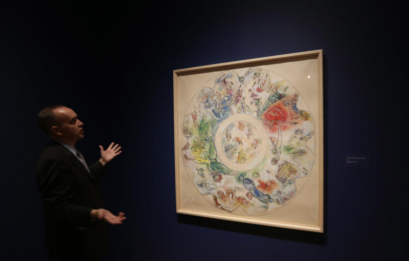 """In this photo taken Feb. 13, 2013 Museum curator Olivier Meslay talks about a 1963 Marc Chagall  piece titled """"Final study for the ceiling of the opera Garnier,"""" included in the """"Chagall: Beyond Color,"""" exhibit during a preview at the Dallas Museum of Art in Dallas.  This will be the only U.S. venue to host the exhibit that opens to the public on Sunday. (AP Photo/LM Otero)"""