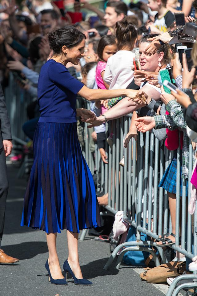 <p>Wearing a bespoke Givenchy jumper and pleated skirt, the Duchess of Sussex stuck to her favourite colour palette while on a walkabout in Rotorua. <em>[Photo: Getty]</em> </p>