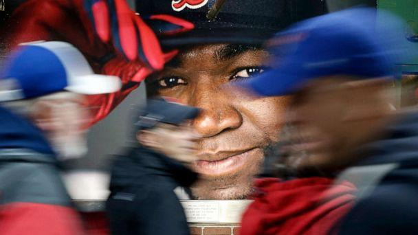 PHOTO: Fans at walk past a photograph of Boston Red Sox's David Ortiz before a baseball game at Fenway Park in Boston, Oct. 1, 2016. (Michael Dwyer/AP, FILE)