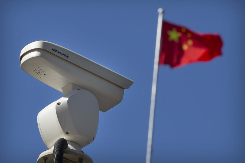 A Chinese flag flies near a Hikvision security camera monitoring a traffic intersection in Beijing, Tuesday, Oct. 8, 2019. The United States is blacklisting a group of Chinese tech companies that develop facial recognition and other artificial intelligence technology that the U.S. says is being used to repress China's Muslim minority groups. (AP Photo/Mark Schiefelbein)