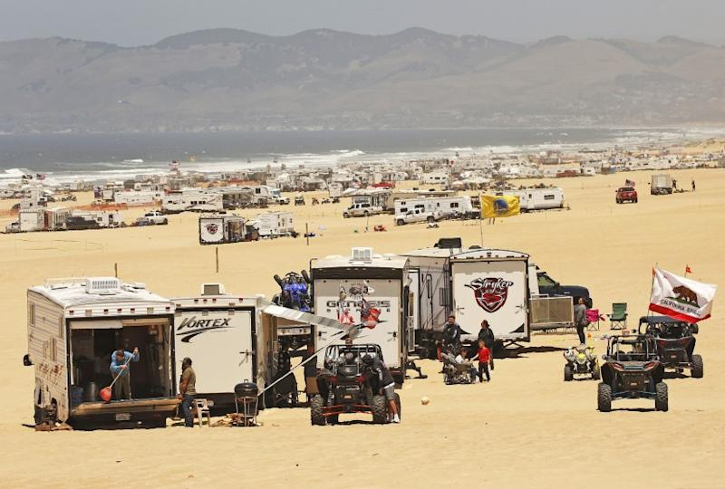 """OCEANO, CA - JULY 03, 2019 - The Oceano Dunes, a few miles south of Pismo Beach off Highway 1, are a major destination for off-roaders and campers, the bulk of them driving in from the Central Valley, Greater Los Angeles or the Bay Area. They arrive in trucks, trailers and RVs and other vehicles, motoring down a ramp onto the beach to access the """"Sand Highway,"""" to make camp July 3, 2019. Oceano Dunes State Park, one of the state's most popular parks draws about 2 million visitors a year. On busy weekends and holidays, reservations for its 1,000 sandy campsites fill up six months in advance. The California Coastal Commission is considering a move to scale back, and potentially eliminate, off-roading at the Oceano Dunes, the only state park on the California coast where you can still ride off-road vehicles. The decision stems from decades of controversy over off roading's impact on sensitive dune habitat, endangered birds and air quality for nearby residents. (Al Seib / Los Angeles Times)"""