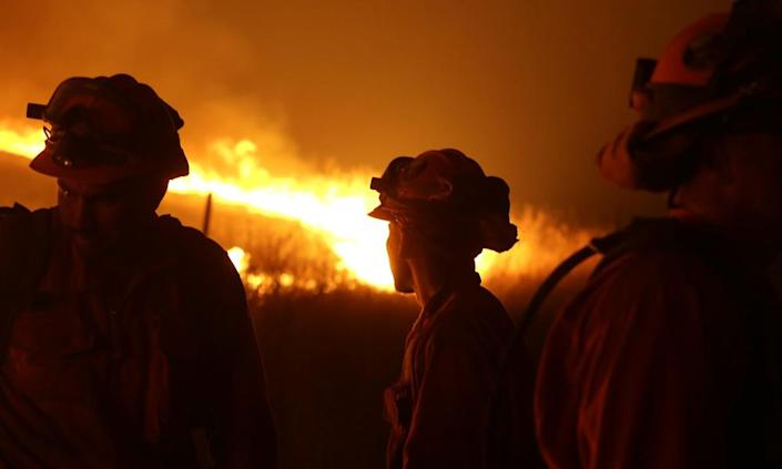 """<span class=""""element-image__caption"""">Incarcerated firefighters stand guard as flames from the Butte fire approach a containment line near San Andreas, California, in 2015.</span> <span class=""""element-image__credit"""">Photograph: Rich Pedroncelli/AP</span>"""
