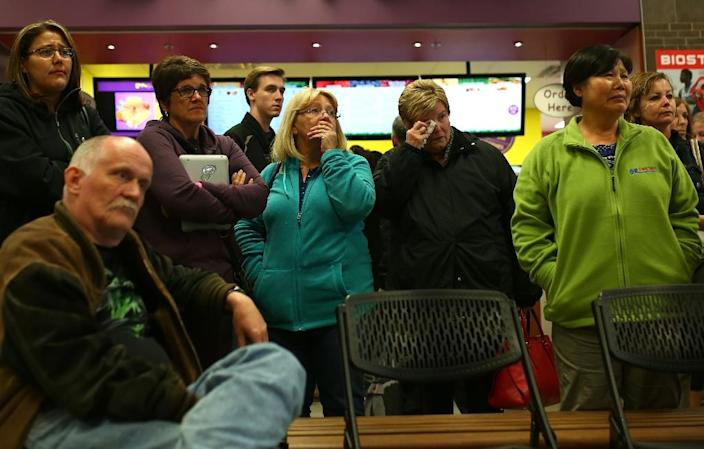 Evacuees react as they watch live footage from inside burned-out neighbourhoods of Fort McMurray on a TV in an evacuee centre in Lac la Biche, Alberta on May 9, 2016 (AFP Photo/)