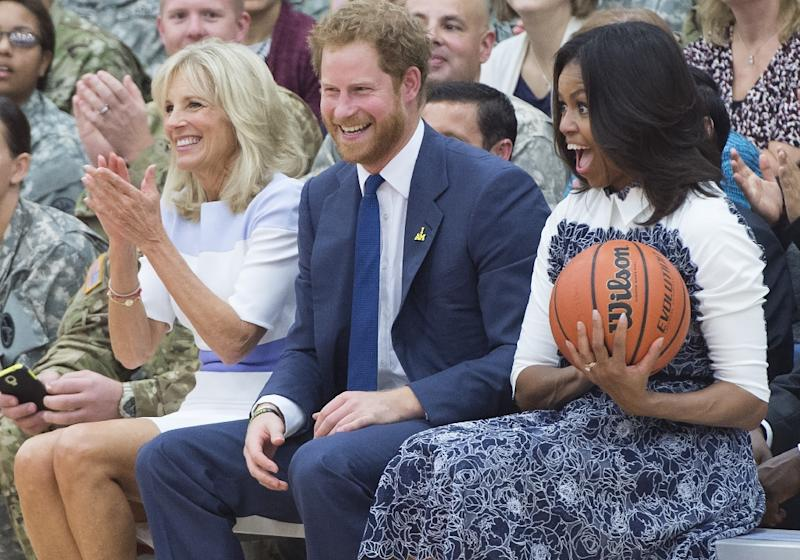 US First Lady Michelle Obama (R) reacts to catching a basketball alongside Britain's Prince Harry (C) and Jill Biden, wife of US Vice President, as they attend Wounded Warriors wheelchair basketball game at Fort Belvoir, Virginia, October 28, 2015 (AFP Photo/Saul Loeb)