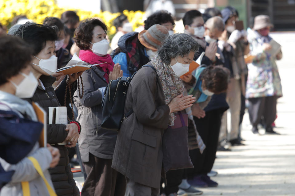 People wearing face masks to help curb the spread of the coronavirus pray during a service at the Chogyesa temple in Seoul, South Korea, Monday, Oct. 19, 2020. South Korea on Monday began testing tens of thousands of employees of hospitals and nursing homes to prevent COVID-19 outbreaks at live-in facilities. (AP Photo/Ahn Young-joon)