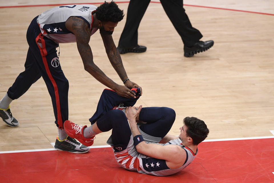 Washington Wizards forward Deni Avdija, bottom, reacts after he was injured during the first half of an NBA basketball game against the Golden State Warriors, Wednesday, April 21, 2021, in Washington. Also seen is Wizards center Jordan Bell (7). (AP Photo/Nick Wass)
