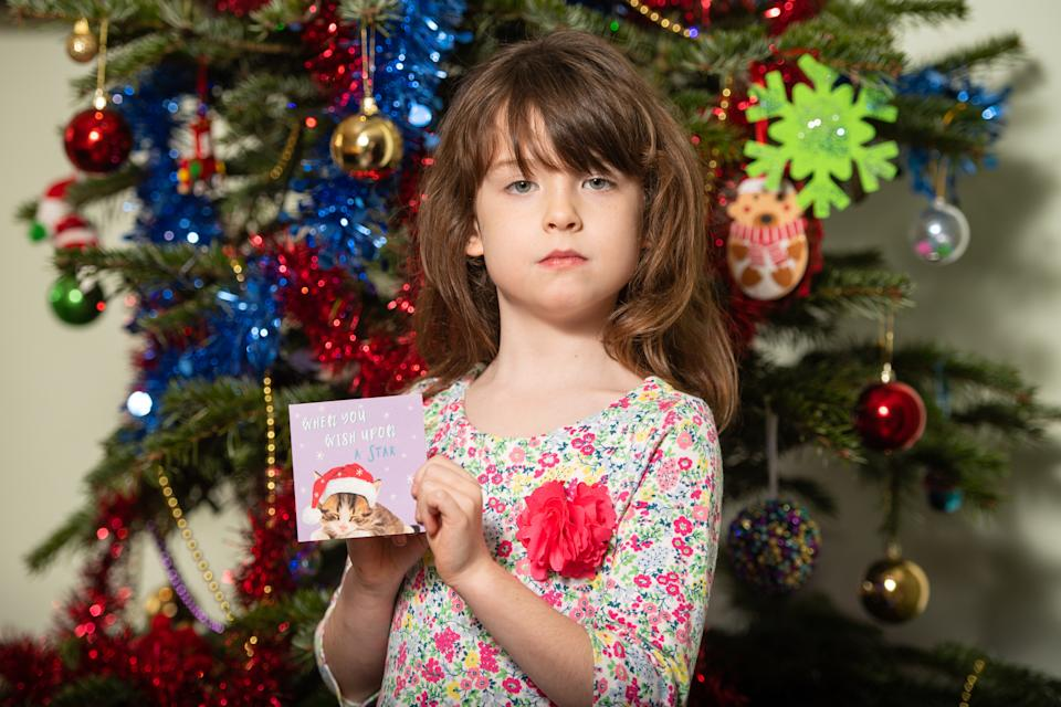 """Florence Widdicombe, 6, at her home in Tooting, south London, holding a Tesco Christmas card from the same pack as a card she found contained a message from a Chinese prisoner. The family who found a message from a Chinese prisoner in a Christmas card said they thought it was a """"prank"""" when they first read it."""