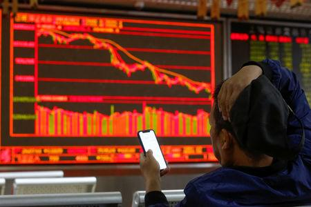 An investor sits in front of displays showing stock information at a brokerage office in Beijing