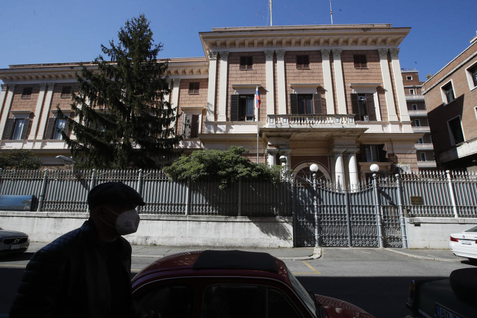 A man walks past the Russian Embassy in Rome, Wednesday, March 31, 2021. Italy has ordered two Russian Embassy officials expelled and arrested an Italian Navy captain on spying charges after police caught the Italian allegedly giving classified documents to one of the Russians in exchange for money. (AP Photo/Alessandra Tarantino)