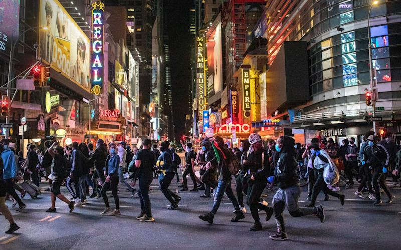 Protesters rush past Times Square after an 11pm curfew during a night of marches and vandalism in NYC - Getty