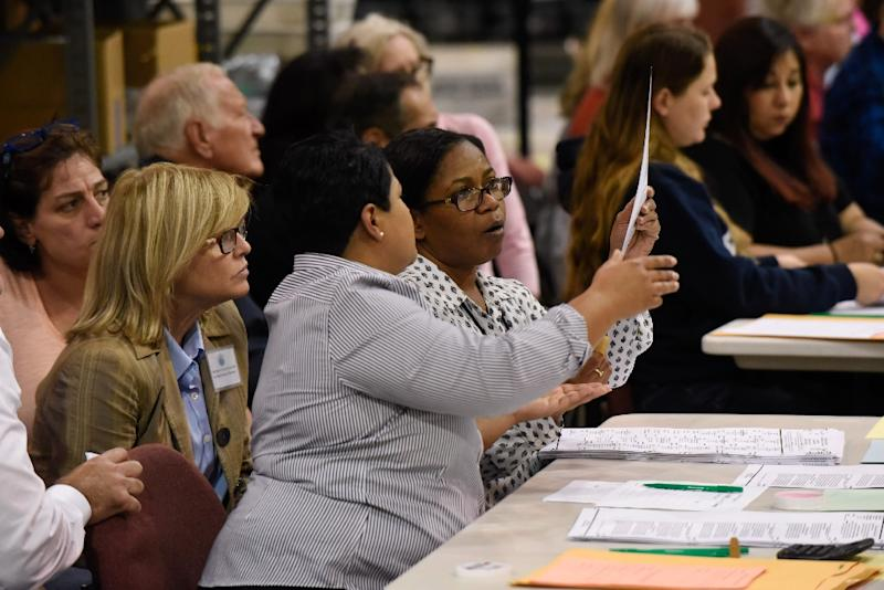 Election officials West Palm Beach examine ballots during a hand recount of votes cast in Florida's hotly contested US Senate race (AFP Photo/Michele Eve Sandberg)