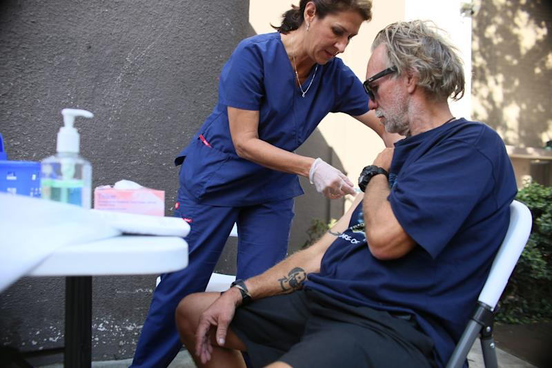 Paulina Bobenrieth, a San Diego county health department nurse, gives a hepatitis A vaccine to a homeless person in the California city on Oct. 4. (The Washington Post via Getty Images)