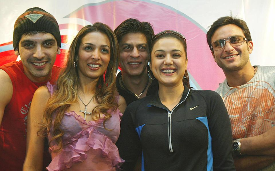 "HONG KONG, CHINA: TO GO WITH ""AFPLIFESTYLE-HONGKONG-INDIA-BOLLYWOOD"" (L to R) Bollywood actors Zayed Khan, Malaika Arora, Shahrukh Khan, Preity Zinta and Saif Ali Khan pose at a press conference in Hong Kong, 30 November 2004. A lavish concert that promies all the fun, passion and fantasy of Bollywood movies hits the stage in Hong Kong this week, hoping to cash in on the growing popularity of the Indian film genre. AFP PHOTO / MIKE CLARKE (Photo credit should read MIKE CLARKE/AFP via Getty Images)"