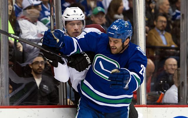 VANCOUVER, BC - APRIL 10: Tom Sestito #29 of the Vancouver Canucks hits Erik Johnson #6 of the Colorado Avalanche along the end boards during the second period in NHL action on April 10, 2014 at Rogers Arena in Vancouver, British Columbia, Canada. (Photo by Rich Lam/Getty Images)
