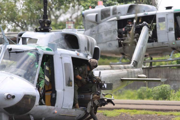 In this image released by the U.S. Marine Corps on Wednesday Aug. 29, 2012, Staff Sgt. Travis A Jakovcic, a UH-1N Huey crew member with Marine Light Attack Helicopter Squadron 467 (HMLA-467) looks back at another aircrew during takeoff at the Guatemalan Air Force Base at Retalhuleu, Guatemala, Aug. 22, 2012. The detachment conducted a mission rehearsal exercise prior to operations beginning in Guatemala. A team of 200 U.S. Marines and four UH-1N Huey helicopters has begun patrolling Guatemala's western coast this week in what a military spokesman says is an unprecedented operation, code named Operation Martillo, to beat drug traffickers in the Central America region. (AP Photo/U.S. Marine Corps)