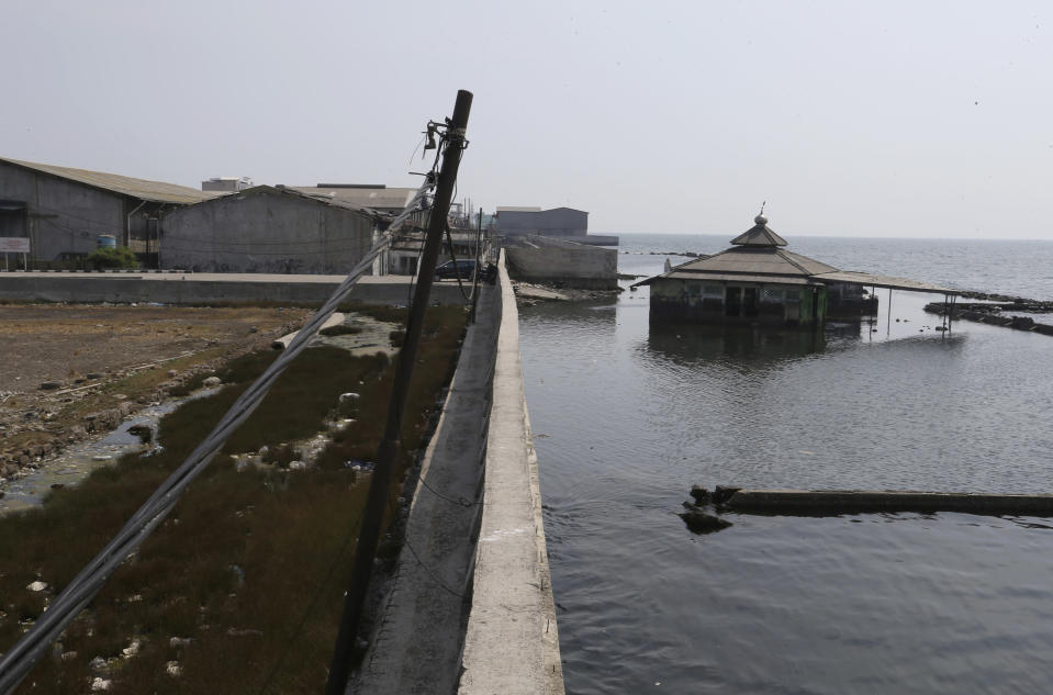 An abandoned mosque stands behind a sea wall which is used as a barrier to prevent sea water from flowing into land and cause flooding in Jakarta, Indonesia, Saturday, July 27, 2019. Indonesia's President Joko Widodo said in an interview that he wants to see the speedy construction of the giant sea wall to save the low-lying capital of Jakarta from sinking under the sea, giving renewed backing to a long-delayed multi-billion-dollar mega project. (AP Photo/Achmad Ibrahim)
