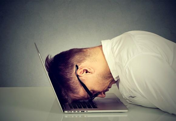 A man with his head bent down and resting on his laptop.