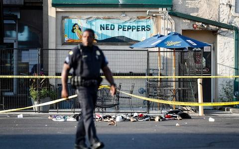 Shoes are piled outside the scene of a mass shooting including Ned Peppers bar - Credit:  John Minchillo