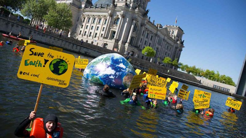 Protesters simulate an end-of-the-world flood theme to advocate urgent climate actions Greenpeace