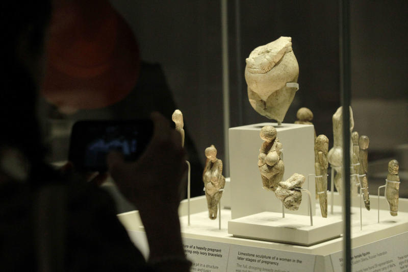 Visitors look at sculptures of pregnant women on display in an exhibition 'Ice Age Art : arrival of the modern mind' at the British Museum in London, Tuesday, Feb. 5, 2013. The exhibition present masterpieces create from the last Ice Age between 40,000 and 10,000 years ago, drawn from across Europe, by artists with modern minds and presented alongside modern works to illustrate the fundamental human desire to communicate and make art as a way of understanding ourselves and our place in the world. (AP Photo/Sang Tan)