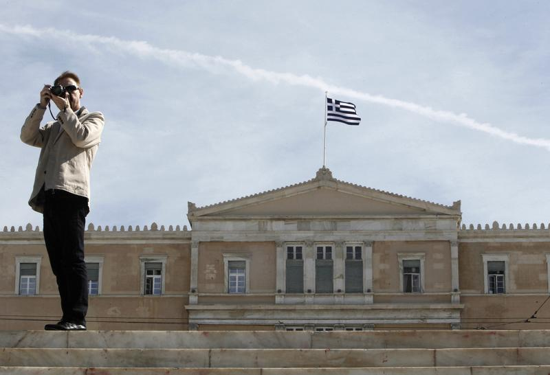 A man takes pictures in front of the parliament in central Athens