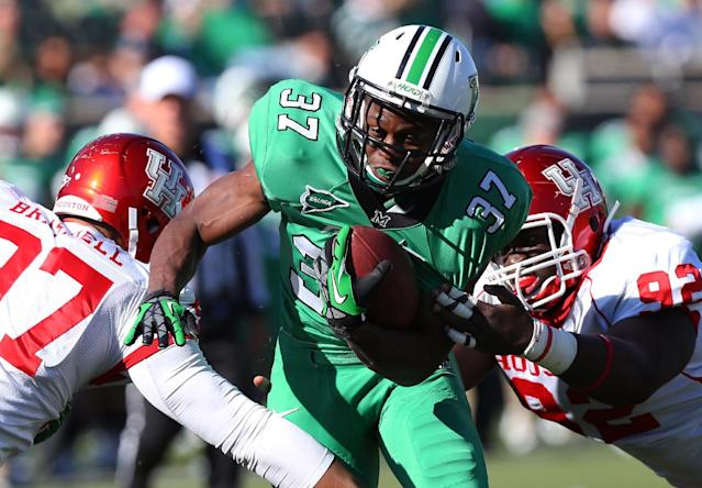 FILE - In a Saturday, Nov. 17, 2012 file photo, Marshall running back Kevin Grooms (37) rushes against Houston defenders Eric Braswell (97) and Joey Mbu (92) during an NCAA college football game, at Joan C. Edwards Stadium in Huntington, W.Va. Marshall University says Grooms has been suspended indefinitely after his arrest early Saturday, Nov. 30, 2013 on charges of misdemeanor domestic battery and obstructing an officer, in Huntington, W.V. (AP Photo/The Herald-Dispatch, Mark Webb, File)