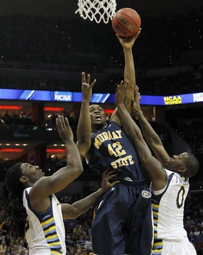 Murray State's Ivan Aska (42) shoots over the defense of Marquette forwards Jae Crowder, left, and forward Jamil Wilson in the first half of their NCAA third-round tournament college basketball game in Louisville, Ky., Saturday, March 17, 2012. (AP Photo/Dave Martin)