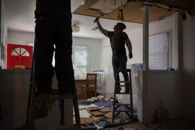 FILE PHOTO: Contractors remove material from a ceiling in a recently-purchased home in Houston
