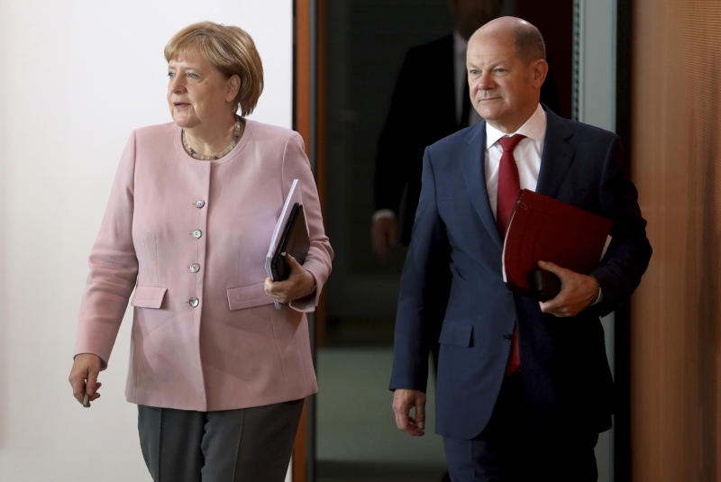 File -- In this Thursday, June 6, 2019 photo German Chancellor Angela Merkel, left, and German Finance Minister and Vice Chancellor, Olaf Scholz, right, arrive for the weekly cabinet meeting at the chancellery in Berlin, Germany. Germany's finance minister is offering to throw his hat in the ring to lead the center-left Social Democratic Party, a traditional powerhouse in German politics that's seen a sharp drop in support in recent years. (AP Photo/Michael Sohn, file)