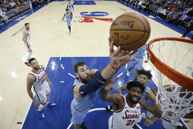 Memphis Grizzlies' Jonas Valanciunas, center, goes up for a shot against Philadelphia 76ers' Joel Embiid during the first half of an NBA basketball game Friday, Feb. 7, 2020, in Philadelphia. (AP Photo/Matt Slocum)