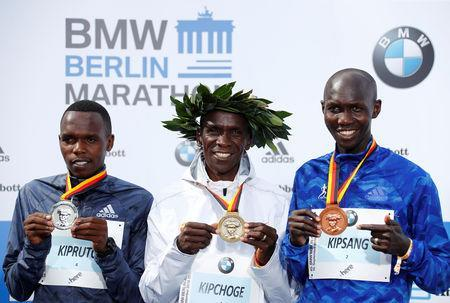 Athletics - Berlin Marathon - Berlin, Germany - September 16, 2018 Kenya's Eliud Kipchoge (C) poses with the medal after winning the Berlin Marathon alongside second placed Amos Kipruto of Kenya (L) and third placed Wilson Kipsang of Kenya (R) REUTERS/Fabrizio Bensch