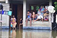 People inside their partially submerged house at flood affected at Baghmari village near Kaziranga in Nagaon District of Assam. (Photo credit should read Anuwar Ali Hazarika/Barcroft Media via Getty Images)