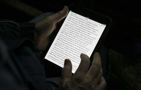 """A man reads the bible from an iPad mini at the """"Christ is the Answer International Ministries"""" group's camp near Florence"""