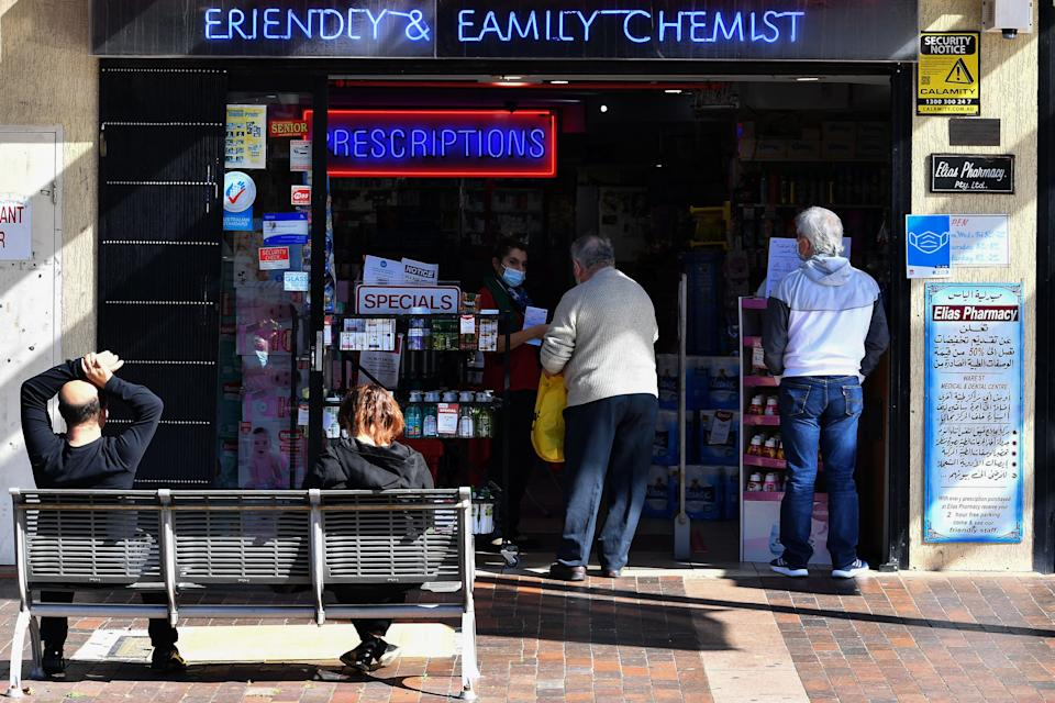 Residents visit a pharmacy in the Fairfield suburb in Sydney on August 2, 2021, during the city's prolonged Covid-19 coronavirus lockdown. (Photo by Saeed KHAN / AFP) (Photo by SAEED KHAN/AFP via Getty Images)