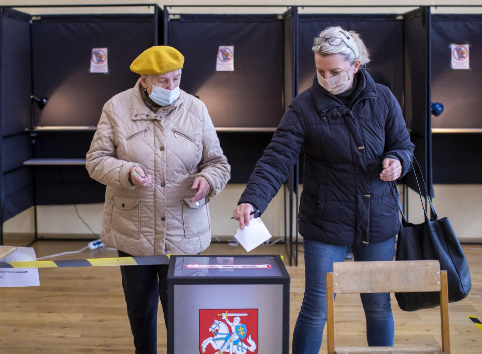 Local residents, wearing face masks to protect against coronavirus, cast their ballots at a polling station during the second round of a parliamentary election in Vilnius, Lithuania, Sunday, Oct. 25, 2020. Polls opened Sunday for the run-off of national election in Lithuania, where the vote is expected to bring about a change of government following the first round, held on Oct. 11, which gave the three opposition, center-right parties a combined lead. (AP Photo/Mindaugas Kulbis)