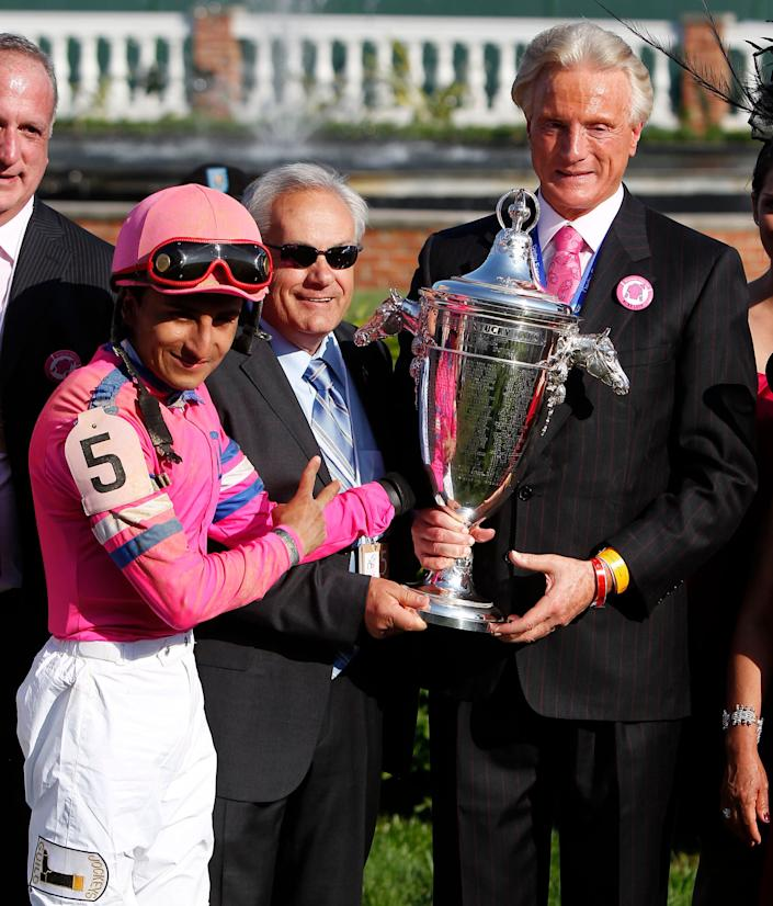 Trainer Jerry Hollendorfer is seen (center) holding the Oaks trophy after his horse Blind Luck won at Churchill Downs in Louisville, Kentucky, in 2010. (Photo: Lexington Herald-Leader via Getty Images)