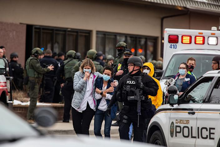 Health care workers walk out of a King Soopers Grocery store after a gunman opened fire on March 22, 2021, in Boulder, Colorado.