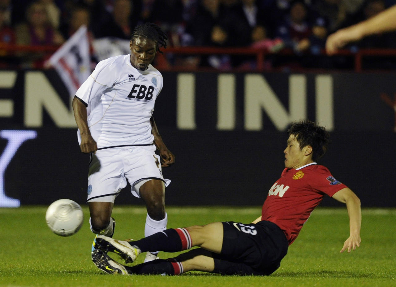 Aldershot Town's Jermaine McGlashan, left, is tackled by Manchester United's Ji-Sung Park during their English League Cup soccer match at the EBB stadium, Aldershot, south of London, Tuesday, Oct. 25, 2011. (AP Photo/Tom Hevezi)