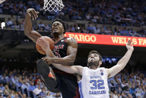 North Carolina's Luke Maye (32) reaches in while Louisville's Steven Enoch (23) drives to the basket during the second half of an NCAA college basketball game in Chapel Hill, N.C., Saturday, Jan. 12, 2019. Louisville won 83-62. (AP Photo/Gerry Broome)